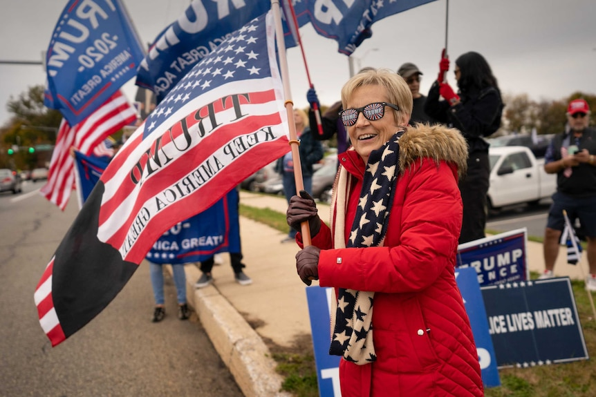A woman in Trump glasses and a red coat, waving an American flag