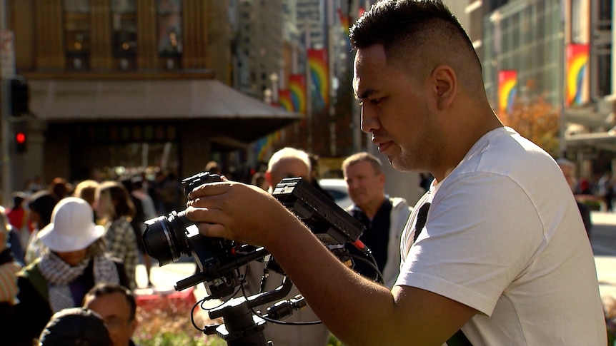 A man looks at a camera as he films in the city, surrounded by people.