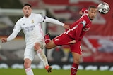 A Liverpool player is challenged for the ball by a Real Madrid opponent during a Champions League match.