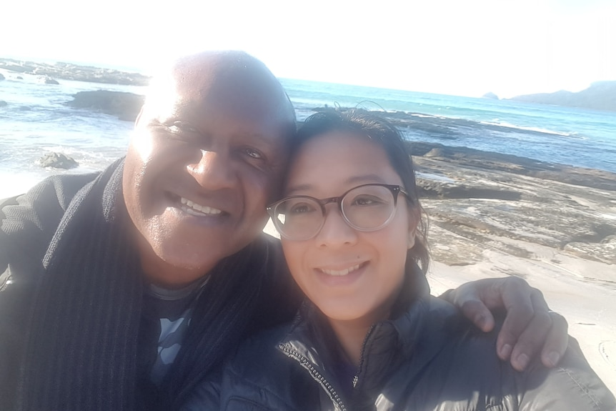 A selfie of a man and woman with their arms around one another's shoulders, smiling, at the beach.