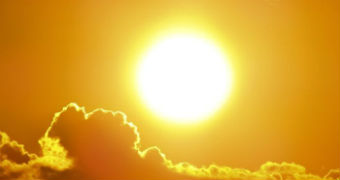 A blazing orange sun sits above golden clouds.