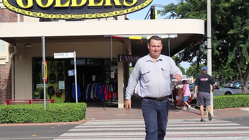 A man walks across a road in front of clothing stores