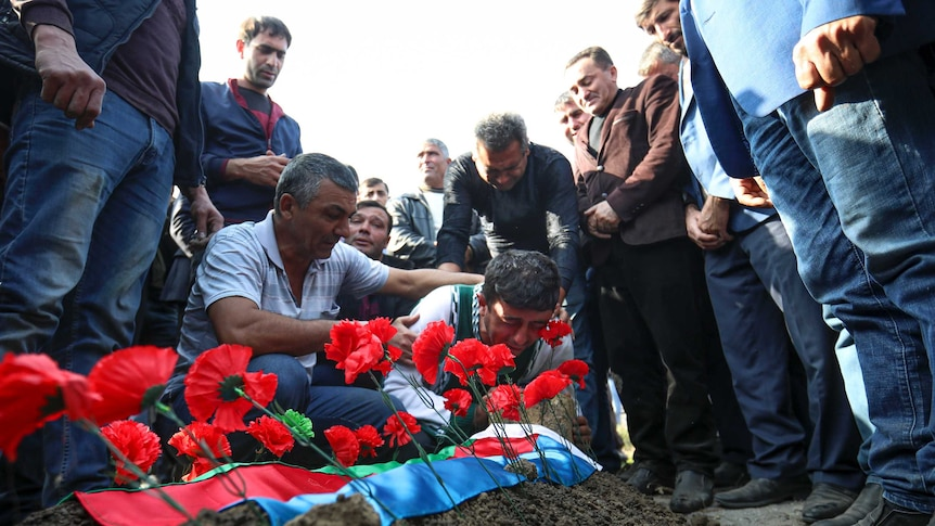 A weeping man crouches over a grave topped with poppies surrounded by a group of men.