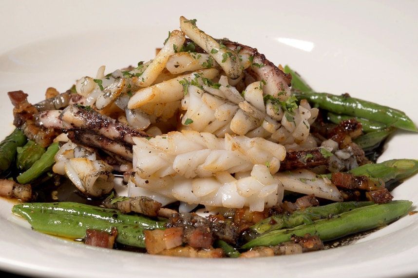 A plate displaying a finished recipe of squid with green beans and chilli pancetta to depict how to prepare and cook squid.