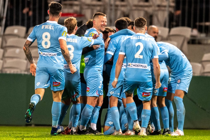 A group of Melbourne City A-League players embrace as they celebrate a goal.
