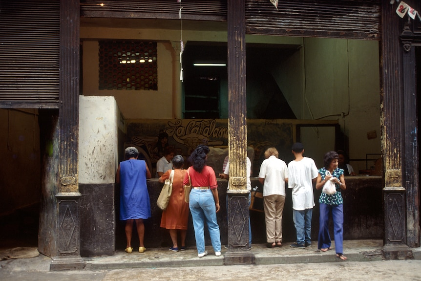 Cuban men and women wait outside a food store in the 1990s.