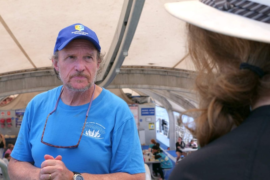 A photo of reef researcher Peter Harrison looking at a tourist on the Great Barrier Reef.