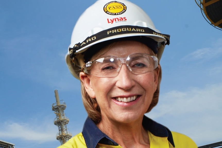 Blonde woman wearing yellow high-vis shirt, white hard hat and safety glasses
