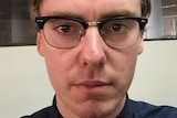 A selfie of a man wearing glasses and looking serious.