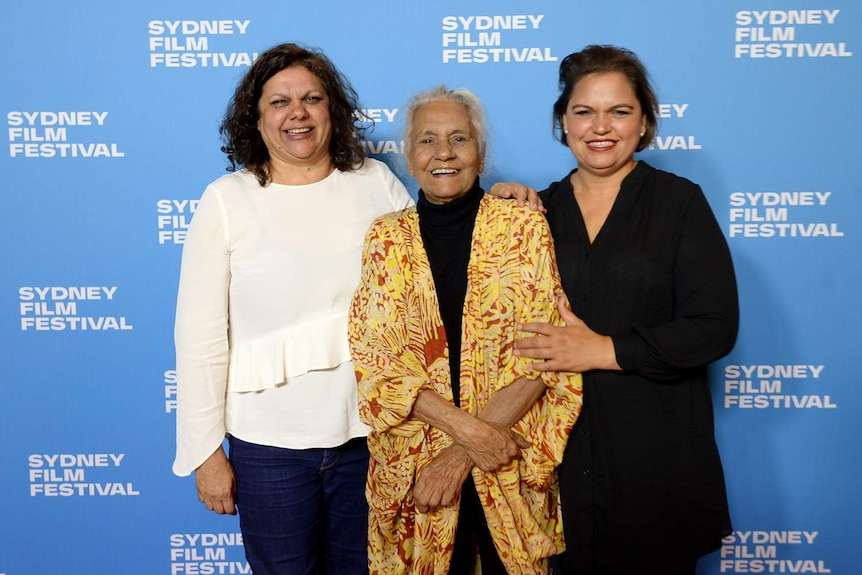 Three women stand smiling with blue SFF-branded wall behind them. Freda Glynn, eldest, in middle.
