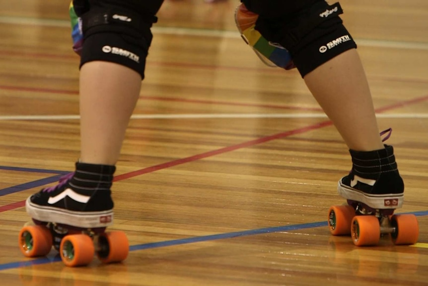 A roller derby competitor wears rainbow kneepads.