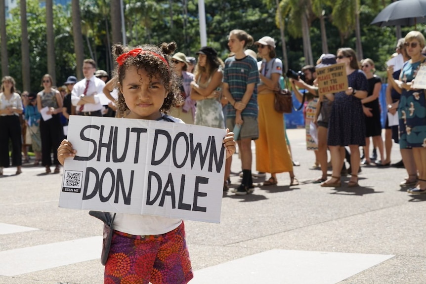 A young girl holds up a 'close Don Dale' sign at a protest against changes to youth bail laws in the NT.