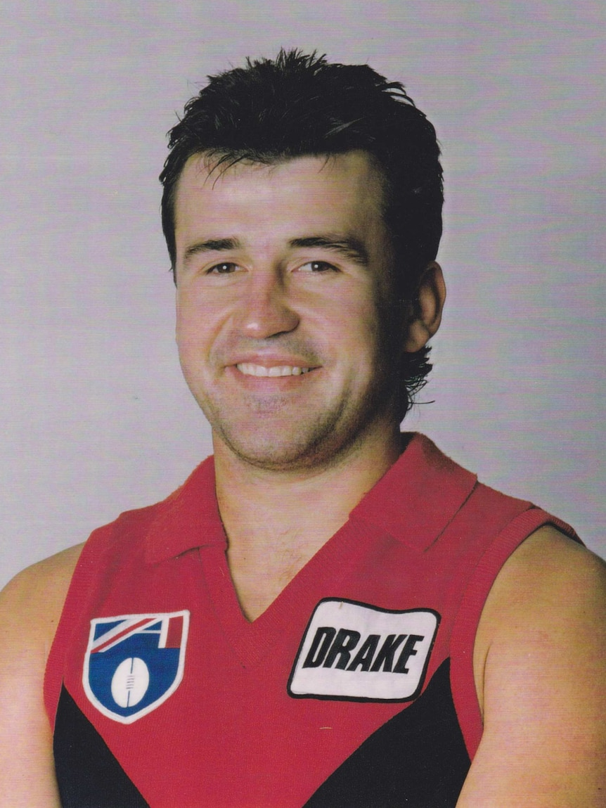 A portrait of a man in a Melbourne Football uniform.