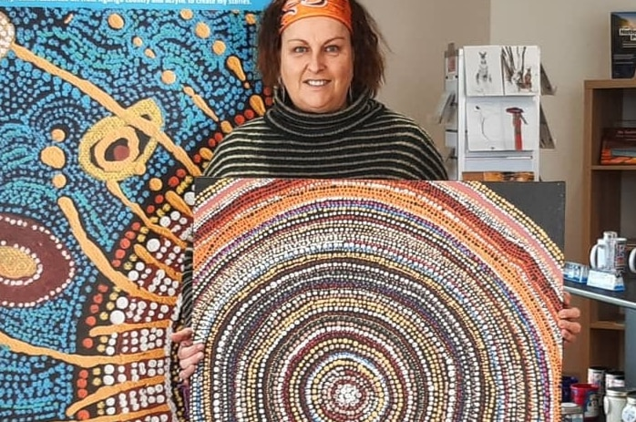 An indigenous artist stands with her painting in a gallery setting.