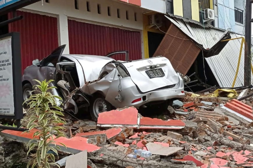 A damaged car and buildings are seen following an earthquake in Mamuju.