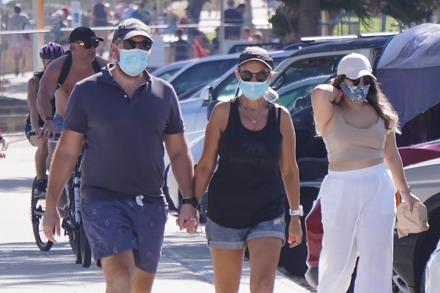 People wearing face masks walk along a footpath at Cottesloe Beach.
