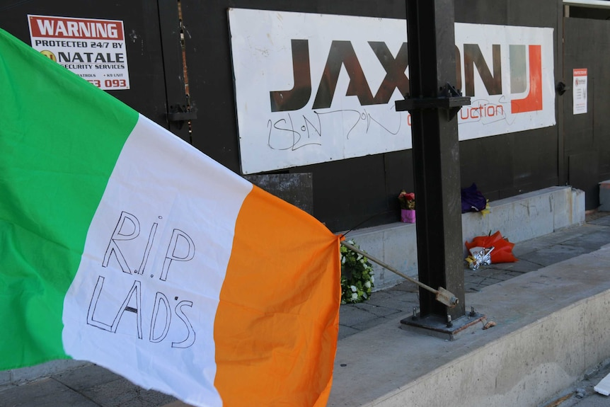 An Irish flag and several bunches of flowers lie outside the entrance to Jaxon construction's East Perth site.