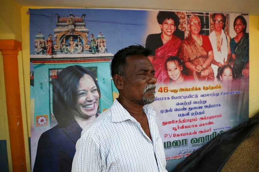 An Indian villager stands in front of a banner displaying photographs of U.S. Vice President-elect Kamala Harris.