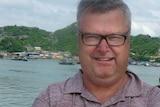 man smiling in front of vietnamese lake