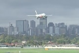 A silver aeroplane lands over a city
