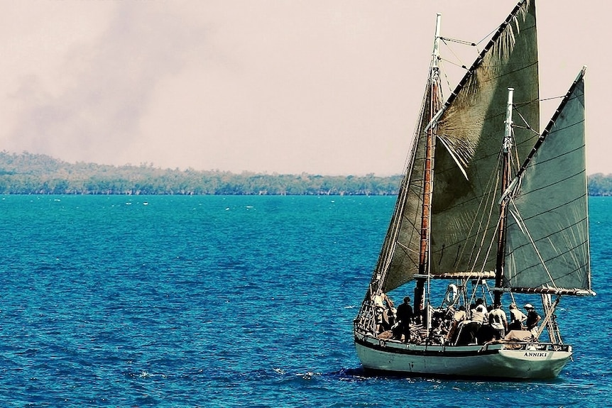 Old wooden sailing ship sailing away from camera toward the mangroves on a nice day.
