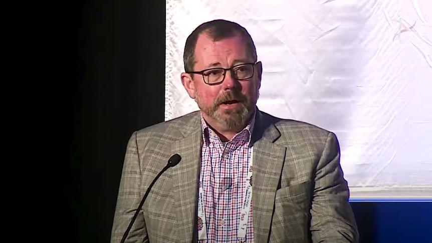 Joe Harman gives a speech at an event.