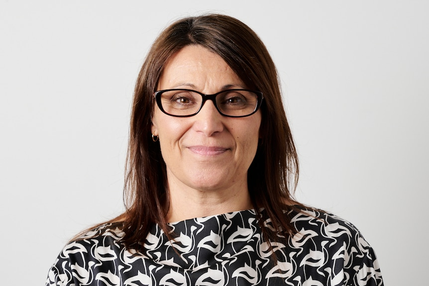 A woman in glasses with brown hair and a black and white top looks at the camera