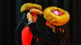 A woman adjusts a flower in another's braids. They are wearing traditional fur hats.