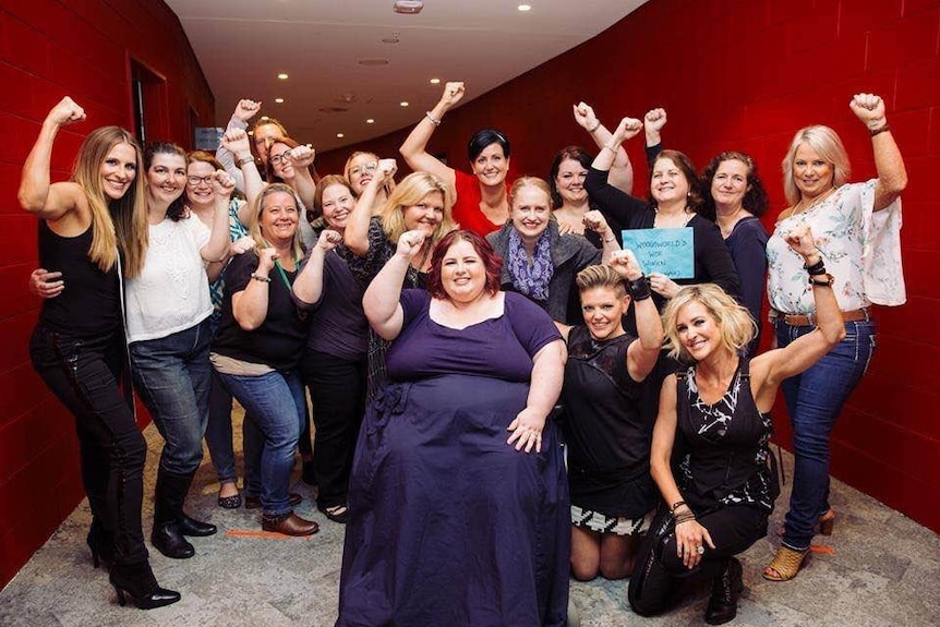 Woman in wheelchair surrounded by a group of women fist pumping