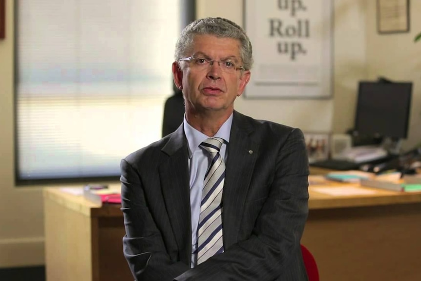 A man looks at the camera in an office