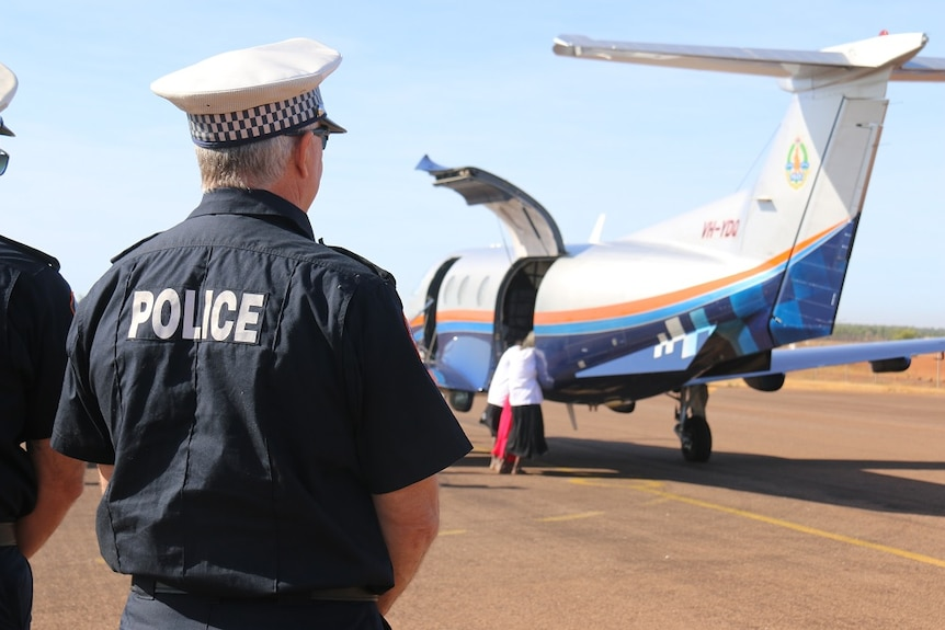 A policeman watches as the body is unloaded from a small plane