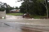 Water from a ruptured water pipe pours down Mt Crosby Road