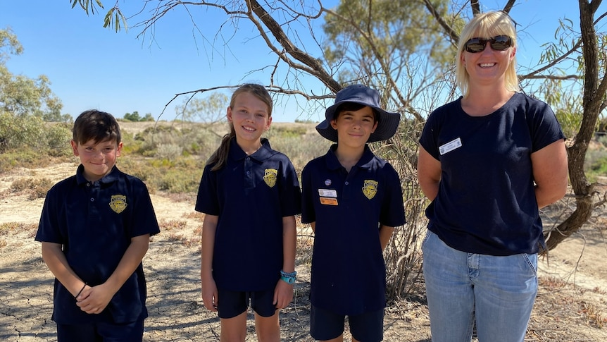 Three children and a woman stand next to each other smiling. There's a blue sky and dry trees and shrubs behind them.