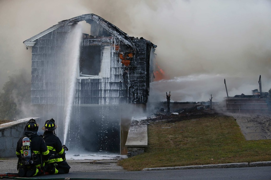 Firefighters hose down a blackened house as they try and extinguish the flames inside