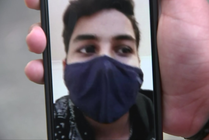 A young man's masked face appears on a video phone call held by a person's hand.