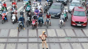 A Vietnam traffic policeman stands in front of waiting motorbikes and cars.
