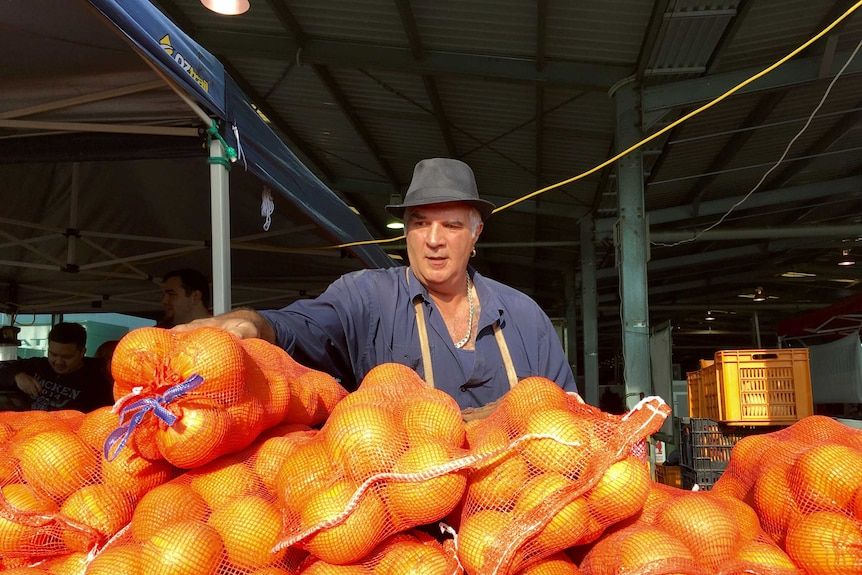 Mick Auddino stands over a bunch of fruit