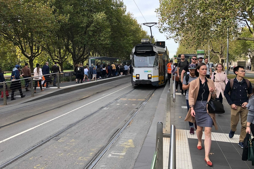 Crowds fill tram platforms at the Art Centre stop.