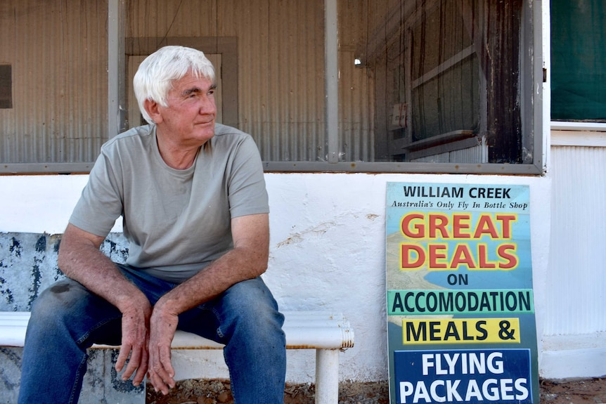 An older man with white hair sits in front of an old building.  The is taring off to his left.