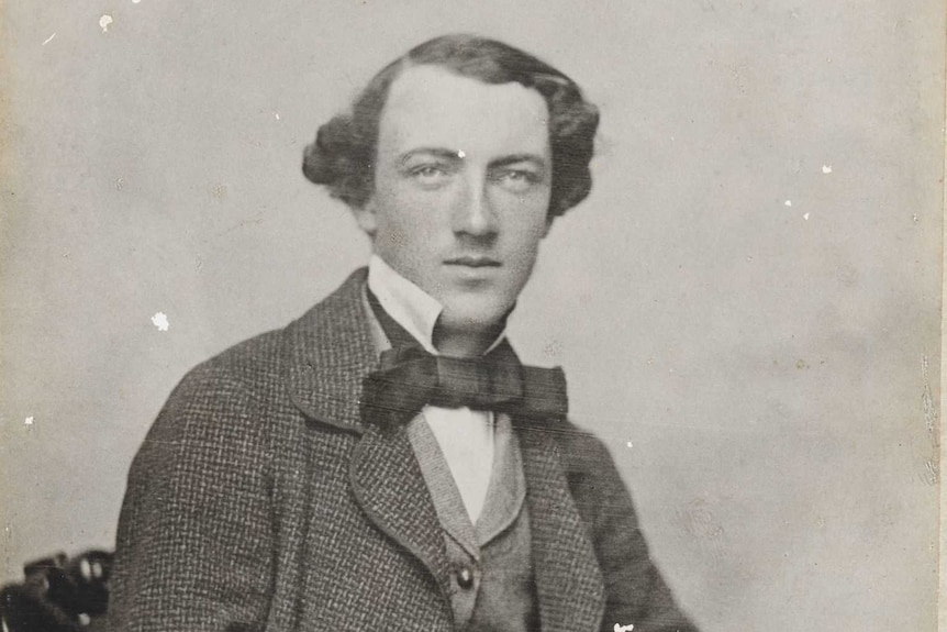 A black and white portrait of Tom Wills.