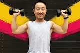 A man holds dumbbells in his hands raised up to head height for a story about weight lifting health benefits.