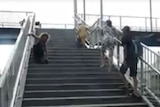 A man without legs climbs up a steep flight of stairs at a train station.