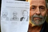 A man with a grey beard holds up a black and white sheet of paper. On it are the pictures of three similar men