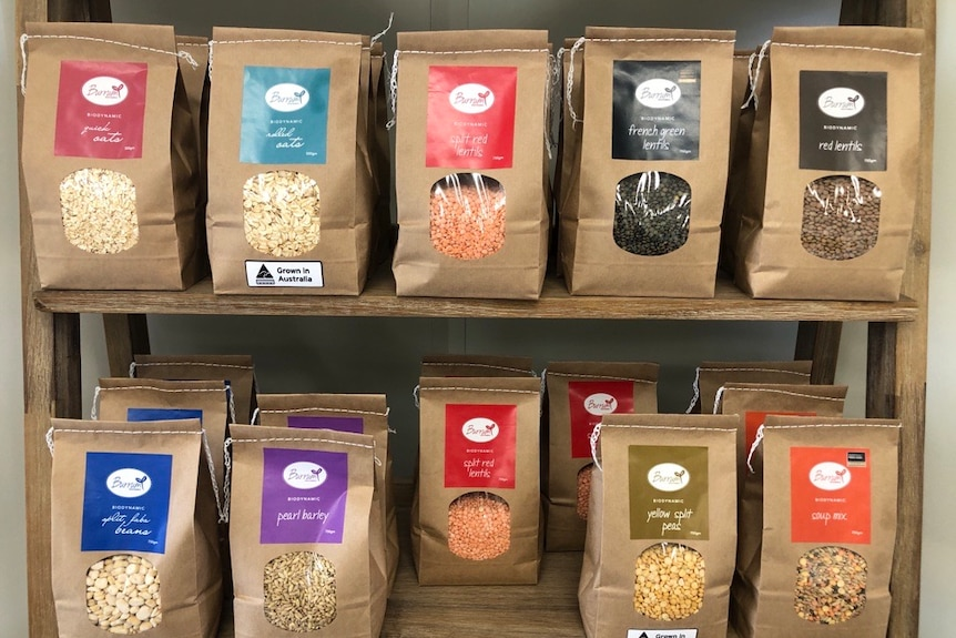 Various coloured packages of grain sit on shelf