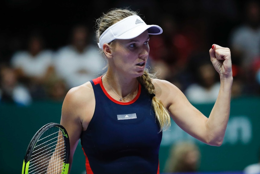 A female tennis player wearing a blue dress with red trim and a white visor cap clenches her fist