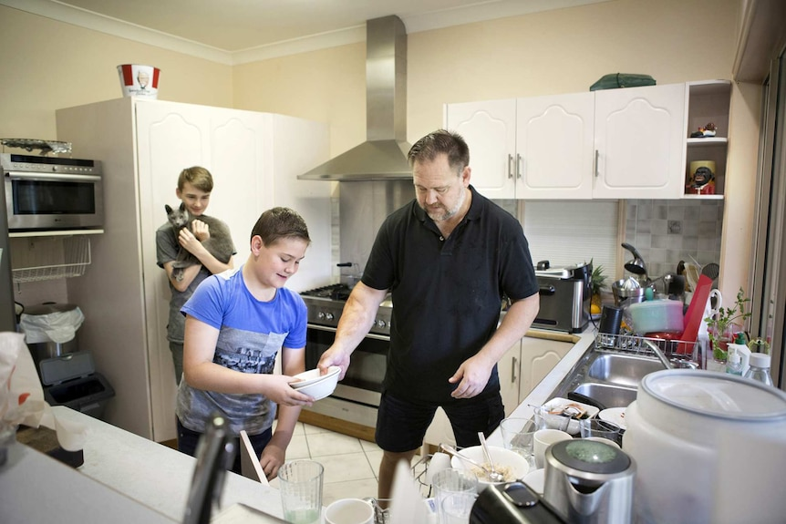 Mark Valencia at home in the kitchen with his two teenage sons