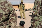 Afghan National Army soldiers watch Australian Sergeant David Nicholls as he demonstrates explosives search techniques.