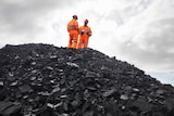 Coal miners on a pile of coal