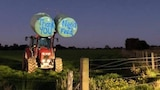 A tractor holding two hay bales with 'thanks need for feed' written on them stands in a paddock.