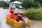 The SES rescuing a man from his flooded home in Townsville
